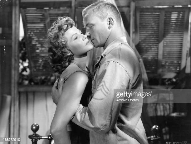 Rita Hayworth with sultry eyes as Aldo Ray embraces her on in a scene from the film 'Miss Sadie Thompson' 1953