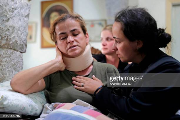 Rita Hitti is comforted by her daughter Karlen during an interview with AFP at their home in the mountain town of Qartaba, north of the Lebanese...