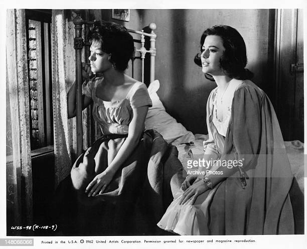 Rita Moreno and Natalie Wood sitting on a bed looking out of a window together in a scene from the film 'West Side Story' 1961