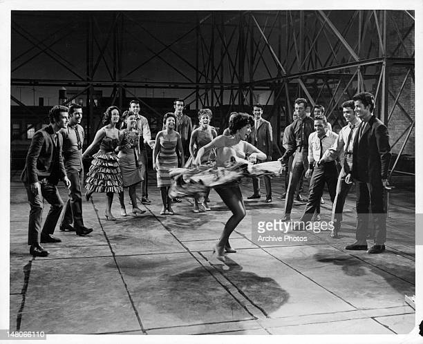 Rita Moreno dancing while surrounded by a group of people that are cheering her on in a scene from the film 'West Side Story' 1961