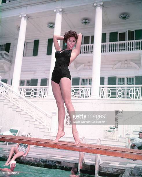 Rita Moreno Puerto Rican singer dancer and actress wearing a black swimsuit posing on a diving board on a swimming pool with swimmers below circa 1955