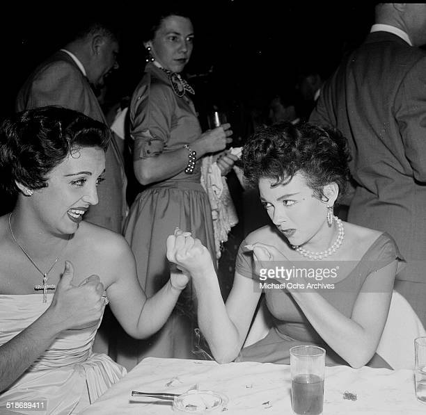 Rita Moreno puts her fists up toward Katy Jurado as they attend a party at Ciro's in Los AngelesCA