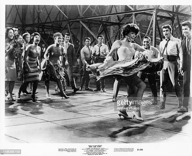 Rita Moreno surrounded by a group of people that are cheering her on while she dances in a scene from the film 'West Side Story' 1961
