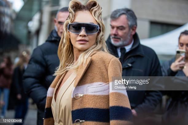 Rita Ora is seen wearing beige striped wool coat, camel overall outside Miu Miu during Paris Fashion Week Womenswear Fall/Winter 2020/2021 : Day Nine...