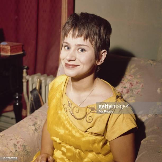 Rita Tushingham British actress smiling while posing in a yellow dress in January 1962