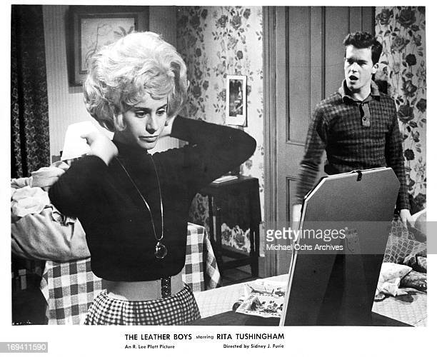 Rita Tushingham works with her blonde hair as Colin Campbell watches in a scene from the film 'The Leather Boys' 1964