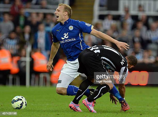 Ritchie De Laet of Leicester City is brought doewn by Yoan Gouffran of Newcastle United during the Barclays Premier League match between Newcastle...