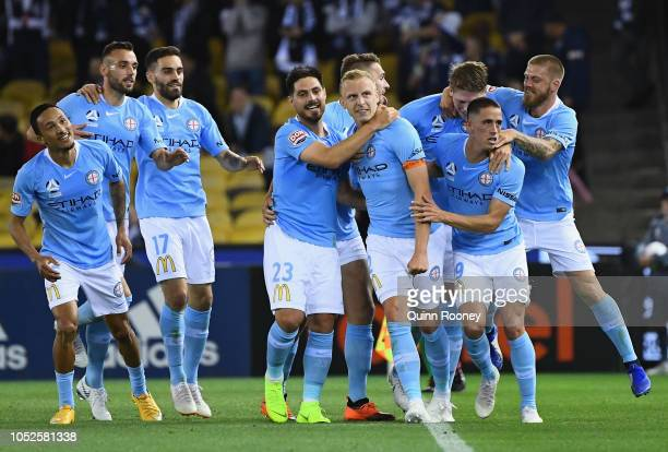Ritchie De Laet of Melbourne City is congratulated by team mates after scoring a goal during the round one ALeague match between Melbourne Victory...