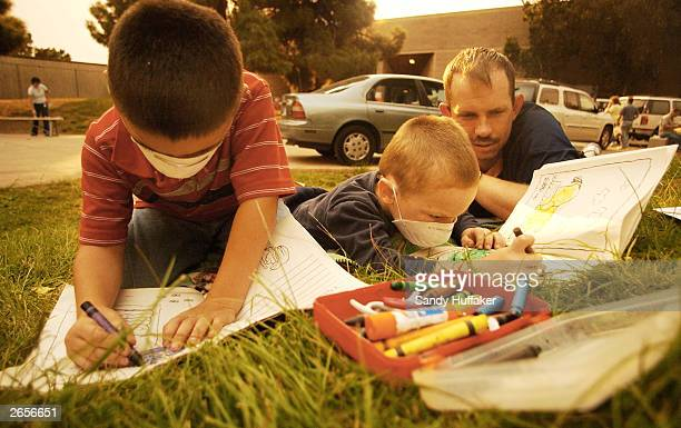 Ritchie Hamilton and his brother Christopher both fouryearsold wear face masks while using crayons to color pictures as their dad Mike Miller looks...