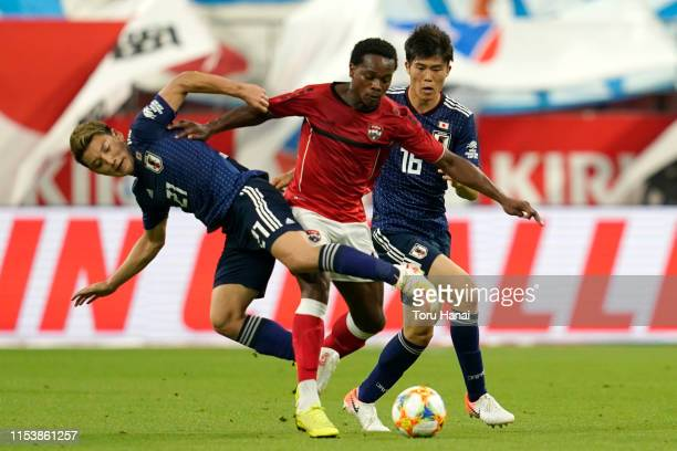 Ritsu Doan and Takehiro Tomiyasu of Japan in action against Levi Garcia of Trinidad and Tobago during the international friendly match between Japan...