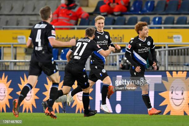 Ritsu Doan of Arminia Bielefeld celebrates with team mates Cedric Brunner and Joakim Nilsson after scoring their side's third goal during the...