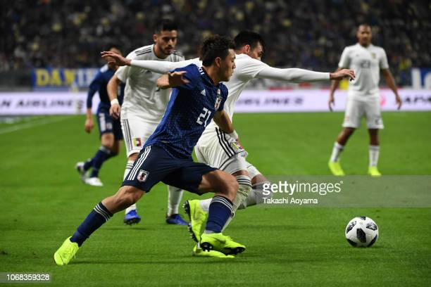 Ritsu Doan of Japan and Luis Mago of Venezuela compete for the ball during the international friendly match between Japan and Venezuela at Oita Bank...