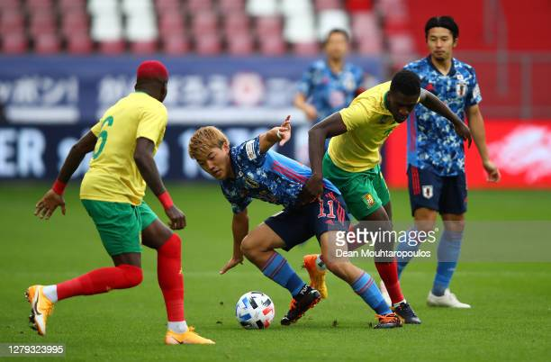 Ritsu Doan of Japan holds off Moumi Ngamaleu of Cameroon during the international friendly match between Japan and Cameroon at Stadion Galgenwaard on...