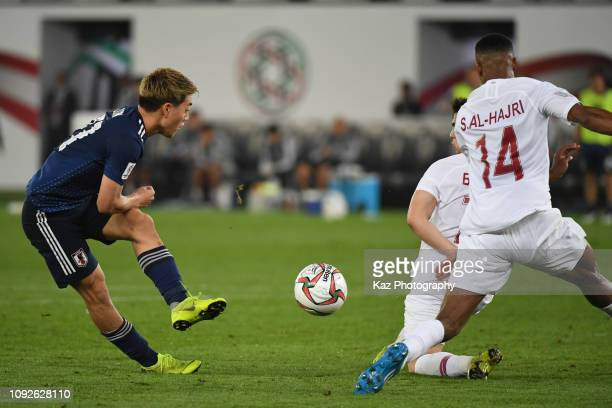 Ritsu Doan of Japan shoots the ball under the challenge from Alrawi Bassam and Al Hajri Salem of Qatar during the AFC Asian Cup final match between...