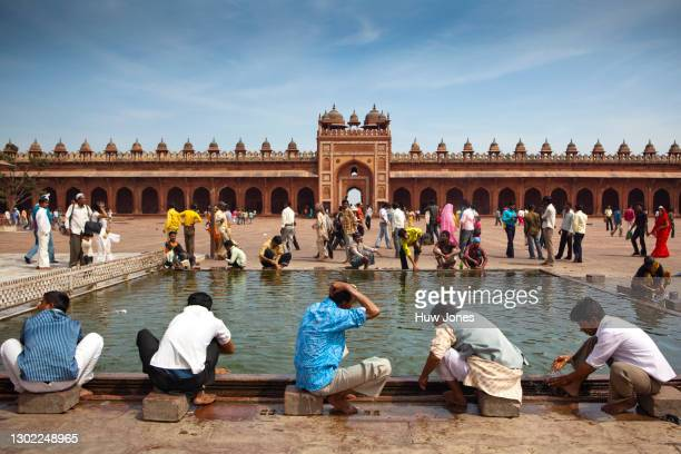 ritual bathing inside the jama masjid mosque, agra, india - agra jama masjid mosque stock pictures, royalty-free photos & images