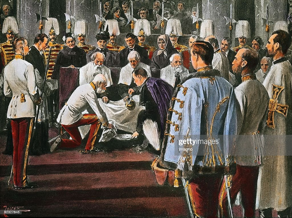 Ritual foot washing by Emperor Franz Joseph I on Maundy Thursday. He is washing the feet of 12 old men and women. In the foreground the Archduke Franz Ferdinand of Austria-Este. Zeremoniensaal (hall). Hofburg. Vienna. Lithograph. Around 1910. : News Photo
