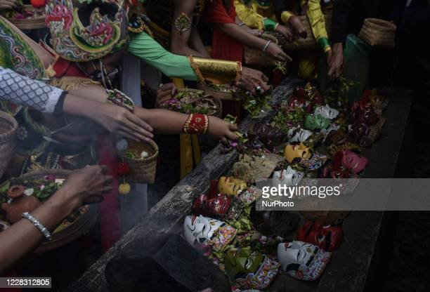 Ritual participants display masks and pray at the tomb area of the creator of the Malangan Mask art in Polowijen village Malang East Java Indonesia...