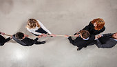 Rival business man and woman compete for the command by pulling the rope