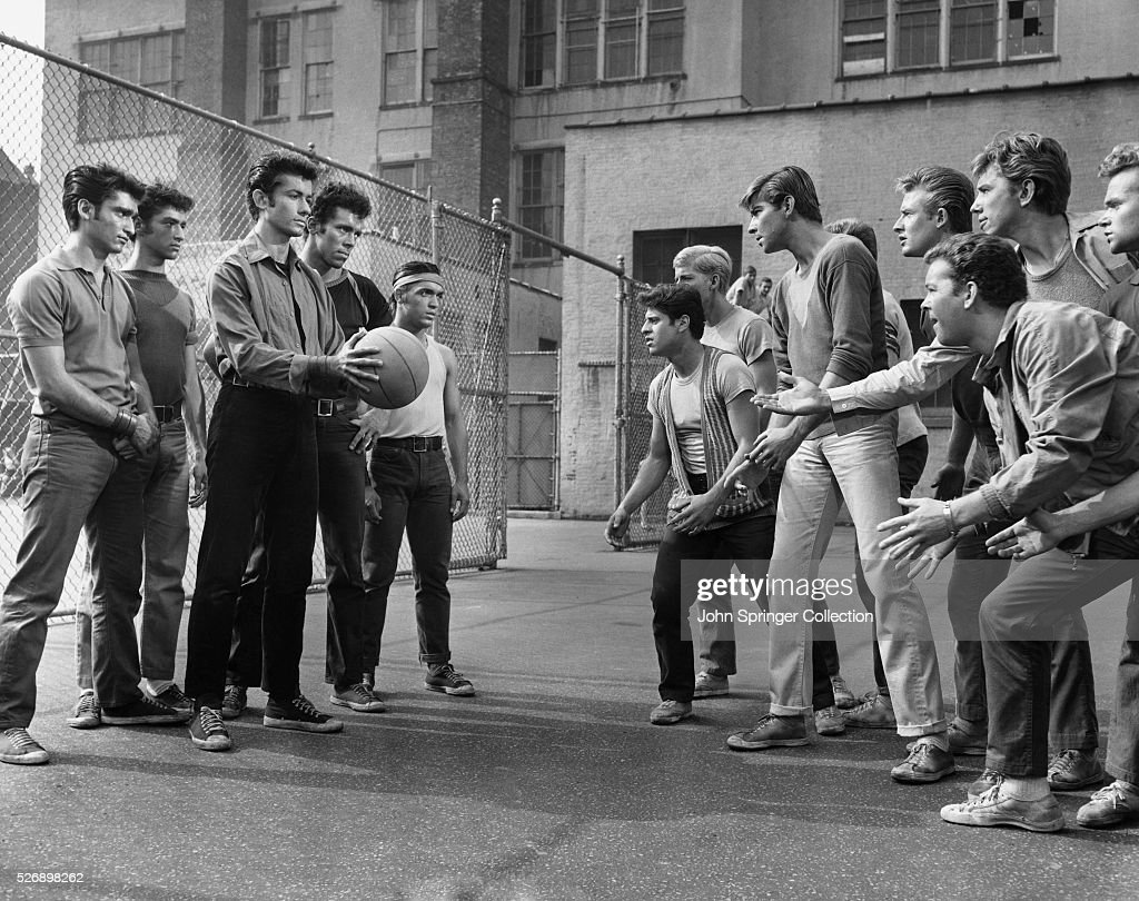 Rival gang members face off in a play yard in a publicity still for West Side Story.