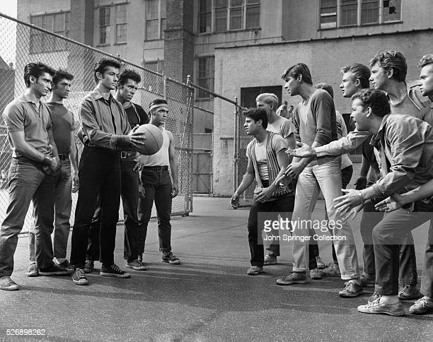 Rival gang members face off in a play yard in a publicity still for West Side Story