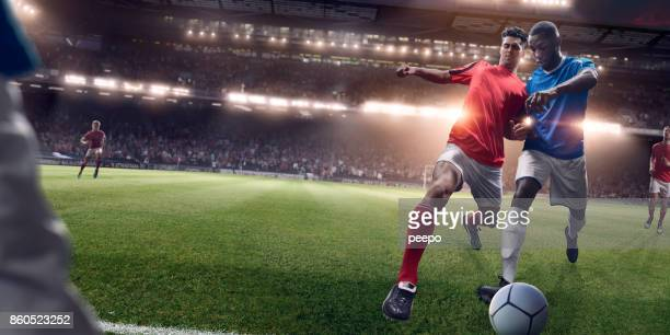rival soccer players in challenge for possession of football - soccer stock pictures, royalty-free photos & images