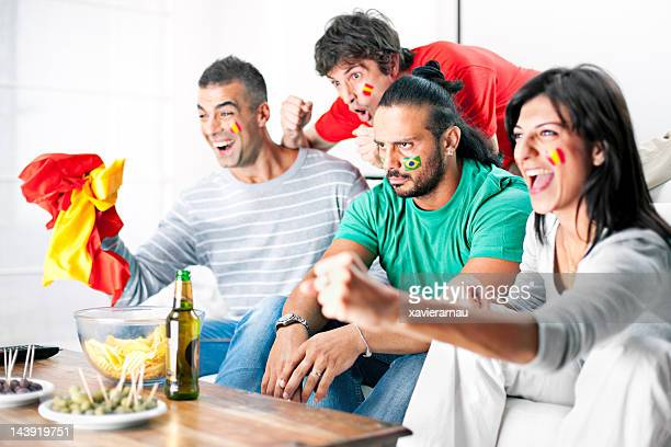 Rival soccer team fans cheering in living room