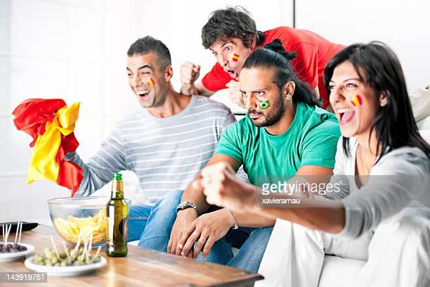 Rivais de equipa de futebol fãs a celebrar em sala de estar