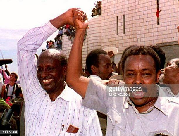 Rival Somali warlords Ali Mahdi and Mohamed Farah Aidid hold hands at a unity rally 28 December 1992 attended by thousands of Somalis from both sides...