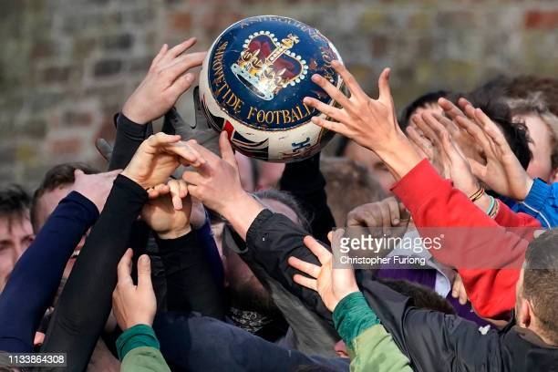 Rival teams the 'Up'ards and Down'ards' battle for the ball during the annual Ashbourne Royal Shrovetide 'no rules' football match on March 05 2019...