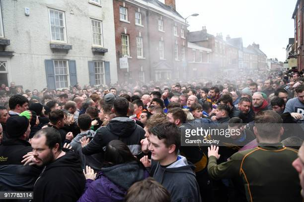 Rival teams 'Up'ards' and 'Down'ards' battle for the ball in the streets during the Royal Shrovetide Football match in Ashbourne Derbyshire England...