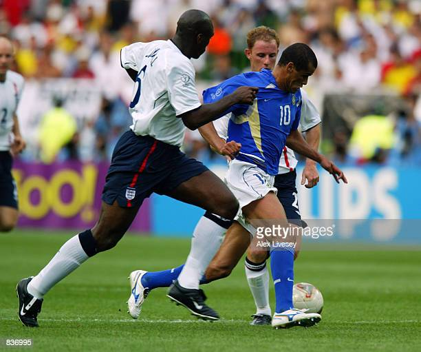 Rivaldo of Brazil takes the ball past Sol Campbell and Nicky Butt of England during the FIFA World Cup Finals 2002 Quarter Finals match played at the...