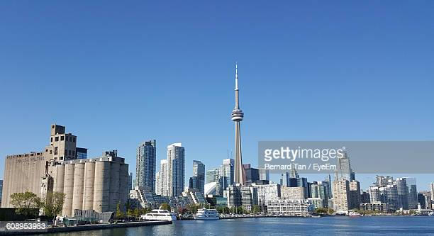 River Against Cn Tower Amidst Modern Buildings Against Clear Blue Sky