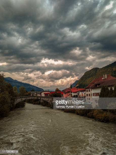 river amidst buildings against cloudy sky - sallanches stock pictures, royalty-free photos & images