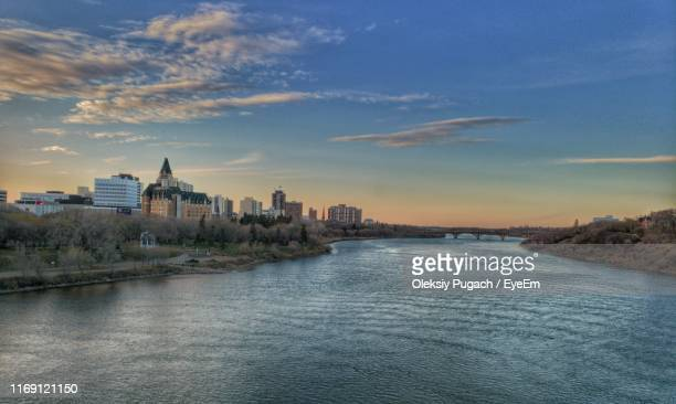 river amidst buildings against sky during sunset - saskatoon stock pictures, royalty-free photos & images