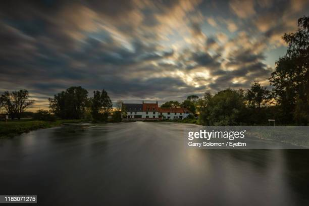 river amidst buildings and trees against sky - great doddington stock photos and pictures