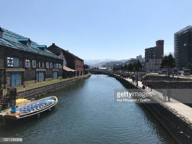 river amidst buildings in city against clear sky - 小樽市 ストックフォトと画像