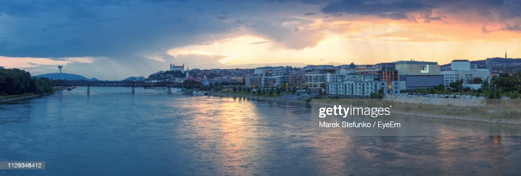River Amidst Buildings In City Against Sky At Sunset : Stock Photo