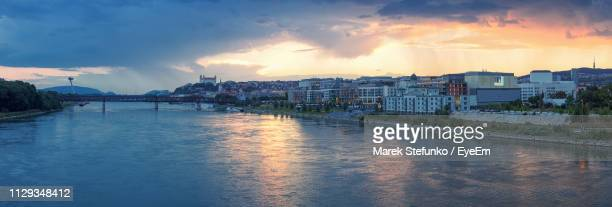 river amidst buildings in city against sky at sunset - marek stefunko stock photos and pictures