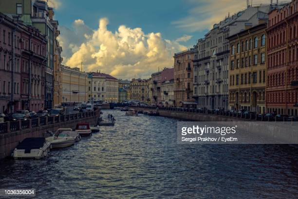 river amidst buildings in city against sky during sunset - sergei stock pictures, royalty-free photos & images