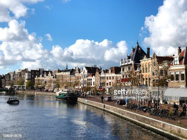 river amidst buildings in city against sky - haarlem stock photos and pictures