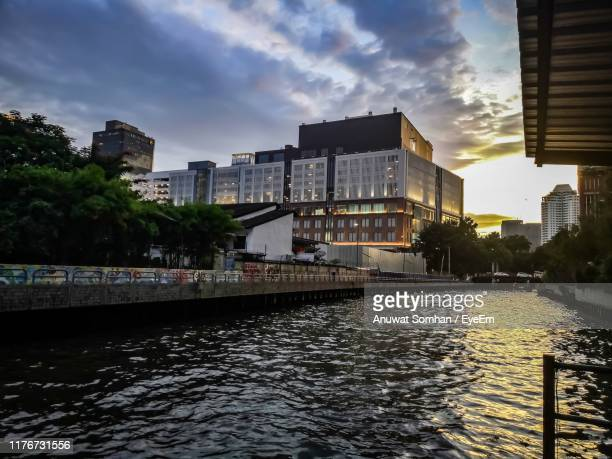 river amidst buildings in city against sky - anuwat somhan stock photos and pictures