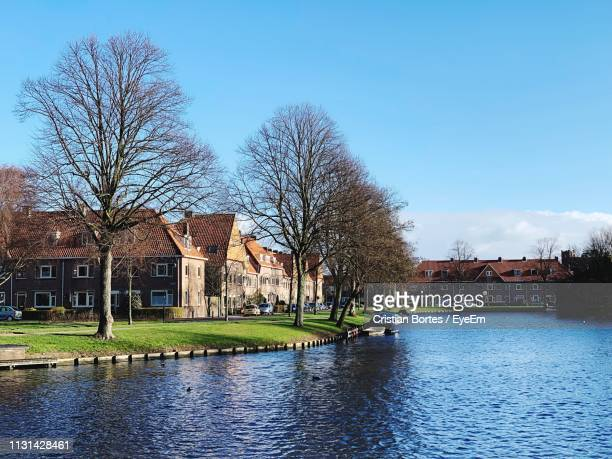 river amidst houses and trees against blue sky - bortes stock pictures, royalty-free photos & images