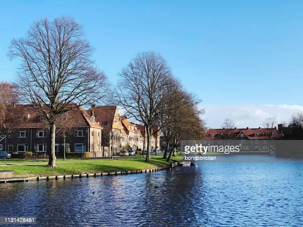 river amidst houses and trees against blue sky - bortes foto e immagini stock