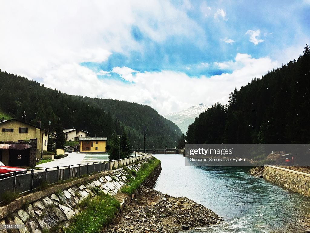 River Amidst Houses And Trees Against Cloudy Sky : Stock Photo