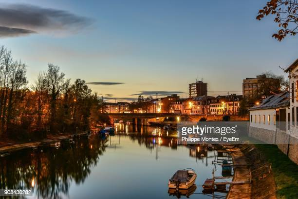 River Amidst Illuminated City Against Sky During Sunset