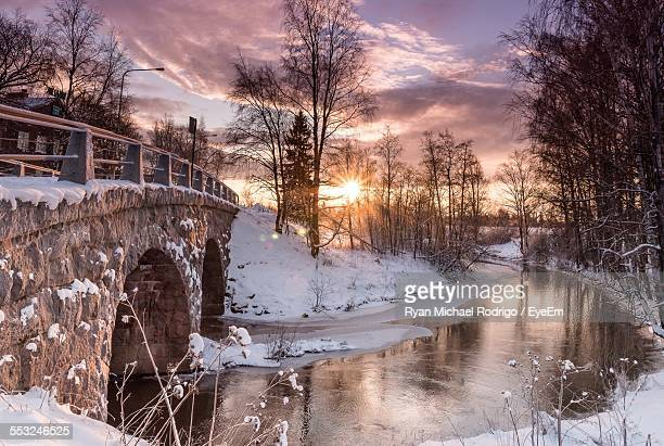 River Amidst Snowcapped Landscape Against Cloudy Sky During Winter