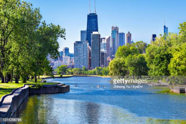river amidst trees and buildings against sky - chicago illinois photos et images de collection