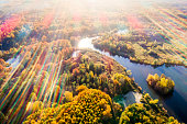 River among Trees. Bird's-eye View with Colorful Sunbeams