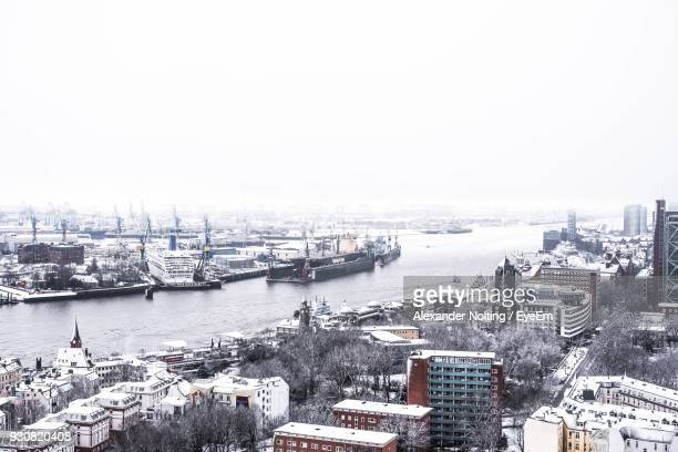 River And Buildings Against Clear Sky During Snowfall