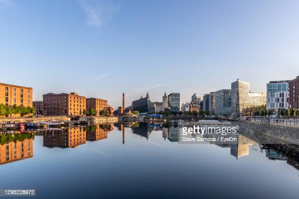 river and buildings against sky at sunrise - liverpool england stock pictures, royalty-free photos & images